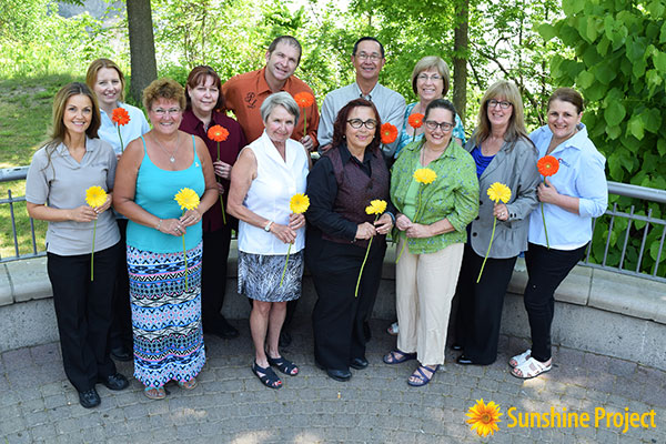 Diverse group of happy, female and male Niagara Casinos associates smiling, holding gerbera daisies symbolizing volunteerism