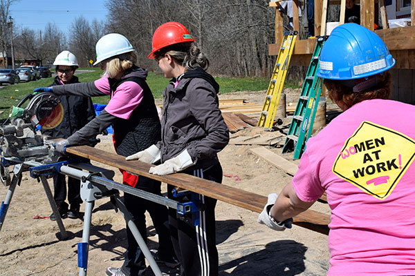 Niagara Casinos female associates using a sliding compound mitre saw as they trim wood, volunteering at Habitat for Humanity