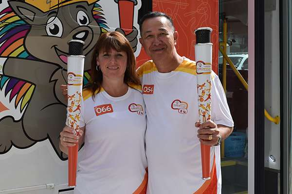 Female and male Niagara Casinos associate smiling, each holding 2015 Pan-Am Games torch, in front of branded bus